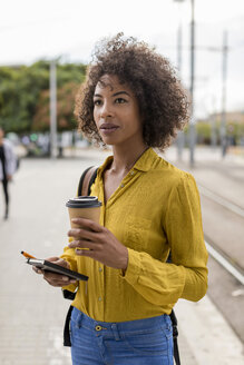 Portrait of woman with coffee to go and notebook in the city - MAUF02330