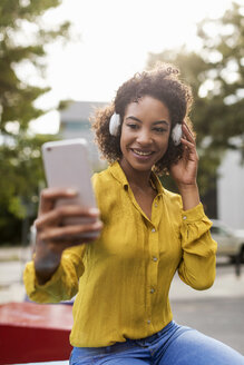 Portrait of smiling woman listening music with headphones taking selfie with smartphone - MAUF02333
