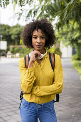 Portrait of woman with headphones and backpack outdoors - MAUF02339