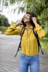 Happy woman listening music with headphones outdoors - MAUF02342