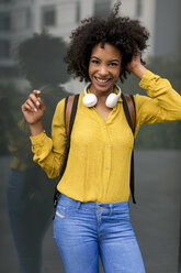 Portrait of laughing woman with backpack and headphones - MAUF02351