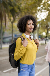 Portrait of woman with backpack and headphones in the city - MAUF02354
