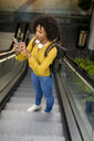 Woman with backpack and headphones standing on escalator using smartphone - MAUF02357