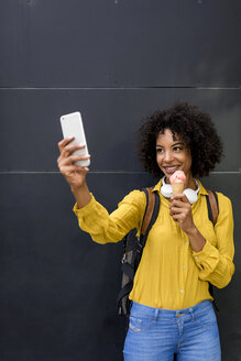 Portrait of smiling woman with ice cream cone taking selfie with smartphone - MAUF02363