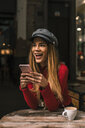 Portrait of laughing young woman sitting on terrace of a coffee shop using smartphone - ACPF00372