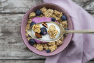 Granola, almonds, blueberry and milk on spoon, close-up - LVF07666