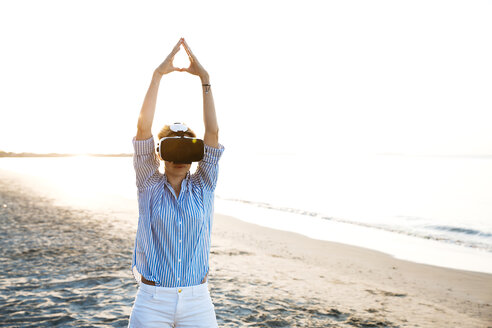 Blonde woman doing kind of yoga exercises on a beach in thailand with 3D virtual reality goggles - HMEF00178