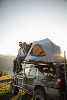 Affectionate couple relaxing at SUV rooftop tent in idyllic mountain field - HEROF06120