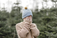 Boy wearing woolen hat covering his face - KMKF00729