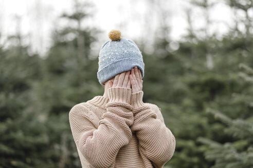 Boy wearing woolen hat covering his face - KMKF00729
