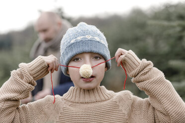 Portrait of a boy putting on woolen nose - KMKF00732