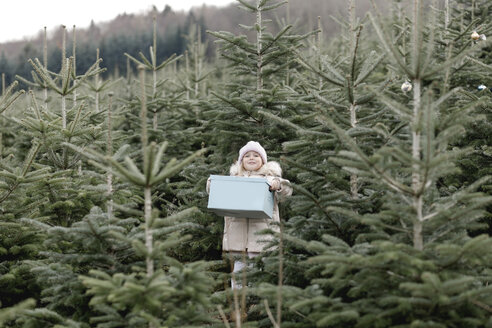 Girl carrying gift box on a Christmas tree plantation - KMKF00735