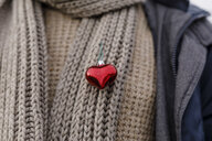 Close-up of man wearing a heart on his scarf - KMKF00747