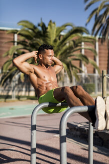 Barechested muscular man doing sit-ups outdoors - MAUF02366