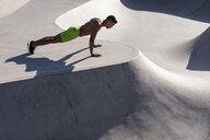 Barechested muscular man doing push-ups in a skatepark - MAUF02378