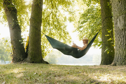 Senior man wearing straw hat relaxing in hammock at lakeshore reading book - GUSF01786