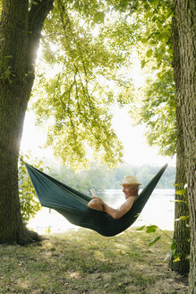 Senior man wearing straw hat relaxing in hammock at lakeshore reading book - GUSF01789