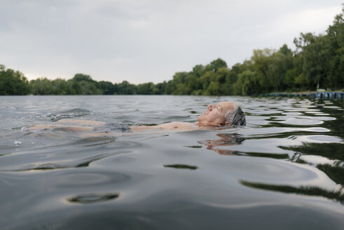 Senior man swimming in a lake - GUSF01792
