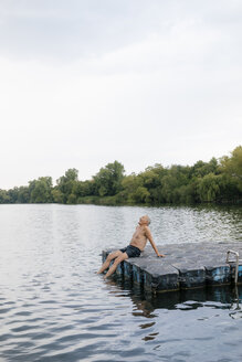 Senior man sitting on raft in a lake - GUSF01804