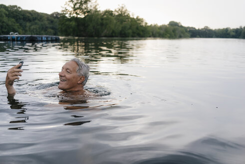 Senior man using cell phone in a lake - GUSF01807