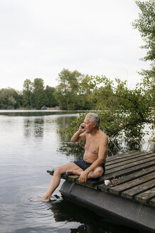 Senior man sitting on jetty at a lake talking on cell phone - GUSF01810