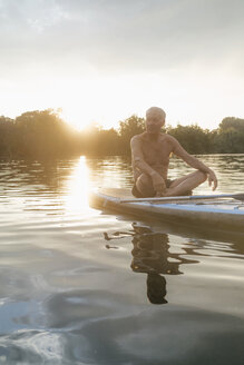 Senior man sitting on SUP board at sunset - GUSF01816