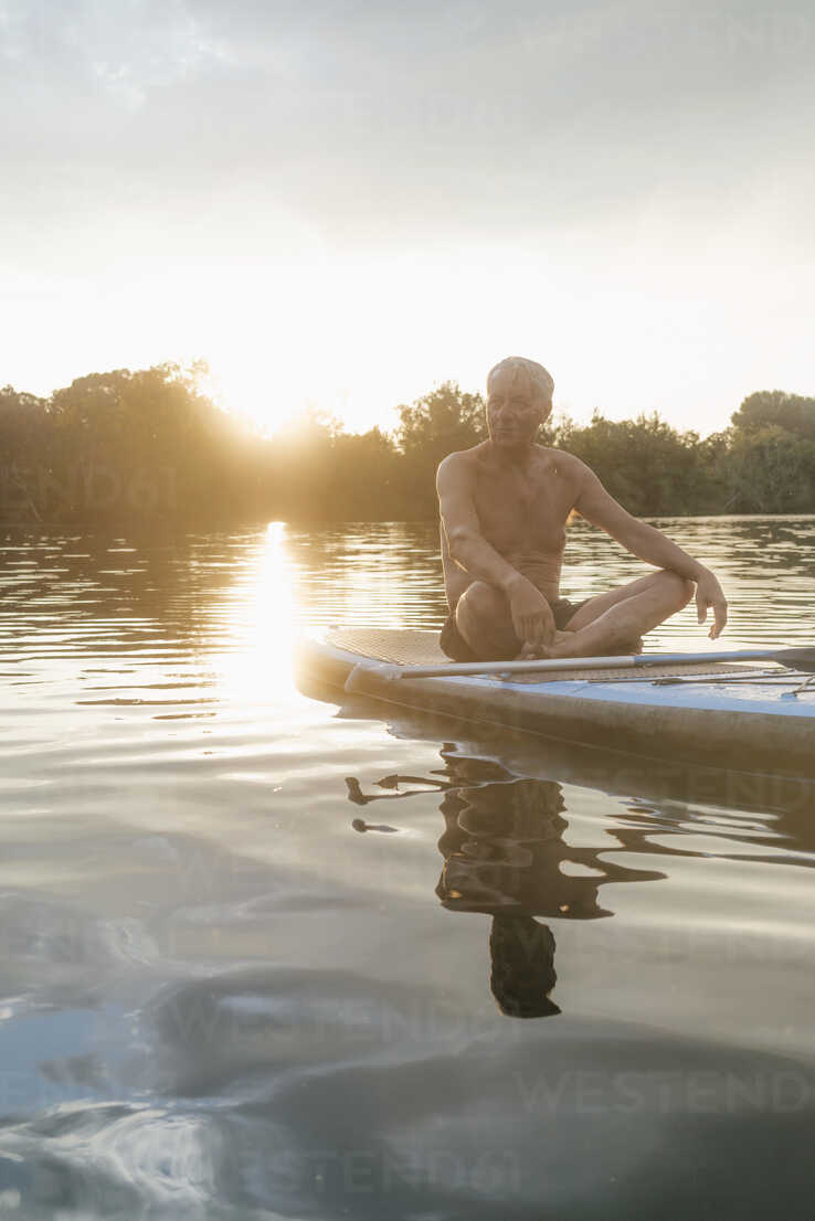 Senior man sitting on SUP board at sunset - GUSF01816 - Gustafsson/Westend61
