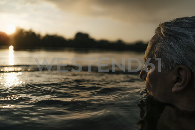 Senior man swimming in a lake at sunset - GUSF01822 - Gustafsson/Westend61