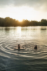 Old and young man swimming in a lake at sunset - GUSF01825