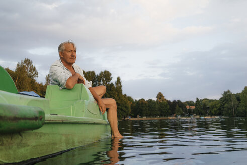 Senior man sitting on paddleboat in a lake - GUSF01828