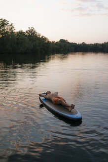 Man lying on SUP board on a lake at sunset - GUSF01831