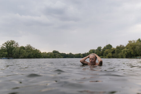 Senior man swimming in a lake - GUSF01834
