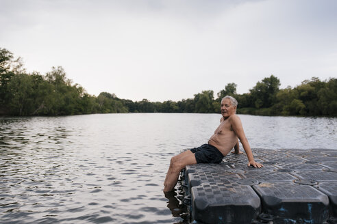 Senior man sitting on raft in a lake - GUSF01837