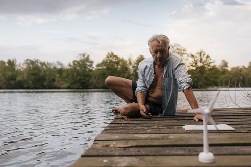 Senior man sitting on jetty at a lake with small wind turbine model - GUSF01846