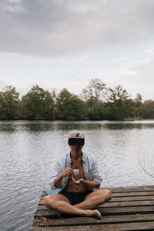 Senior man sitting on jetty at a lake wearing VR glasses and drinking coffee - GUSF01849