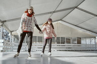 Mother holding hand of her daughter , while ice skating - ZEDF01785