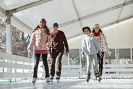 Family with two kids ice skating on the ice rink - ZEDF01788
