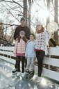 Family leaning on railing at the ice rink - ZEDF01794