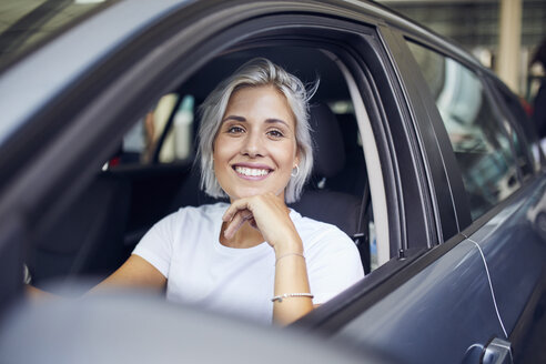 Young woman sitting in her car - PNEF01146