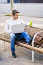 casual businessman sitting on a bench, working relaxed in the city - GIOF05586