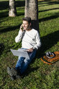 casual businessman sitting on grass in a park, using laptop, talking on the phone - GIOF05616