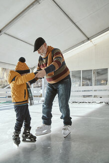 Grandfather and grandson on the ice rink, ice skating - ZEDF01808