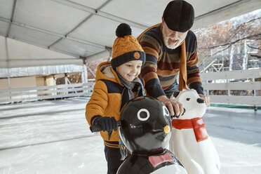 Grandfather and grandson on the ice rink, ice skating, using ice bear figure as prop - ZEDF01811