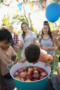 Boy bobbing for apples at summer neighborhood block party in park - HEROF06149