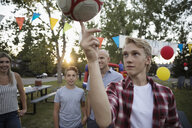 Boy balancing soccer ball on finger at summer neighborhood block party in park - HEROF06155