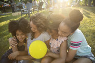 Affectionate mother and daughters with balloon hugging at summer neighborhood block party in park - HEROF06161