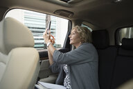 Businesswoman using camera phone, leaning out window of crowdsourced taxi - HEROF06218