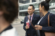 Businessman and businesswoman with coffee talking on urban sidewalk - HEROF06257