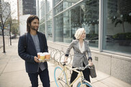 Business people with bicycle and coffee walking on urban sidewalk - HEROF06263