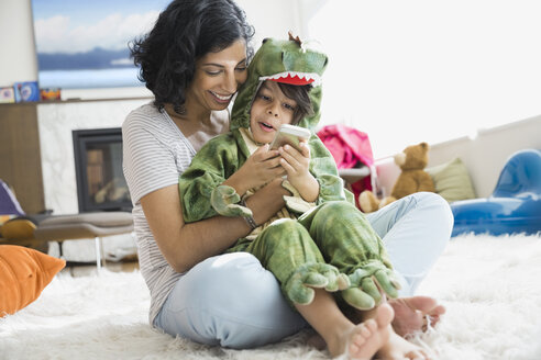 Mother holding son in dragon costume - HEROF06407